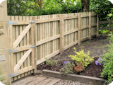 Feather edge wooden fence cladding using (and hiding in the process) original concrete fence posts in a Bolton garden.