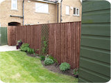 Feather edge wooden fence cladding in a Bolton garden.