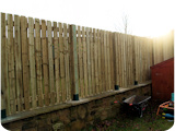 Post rail and pale fencing fitted to the top of an existing wall in Rochdale.